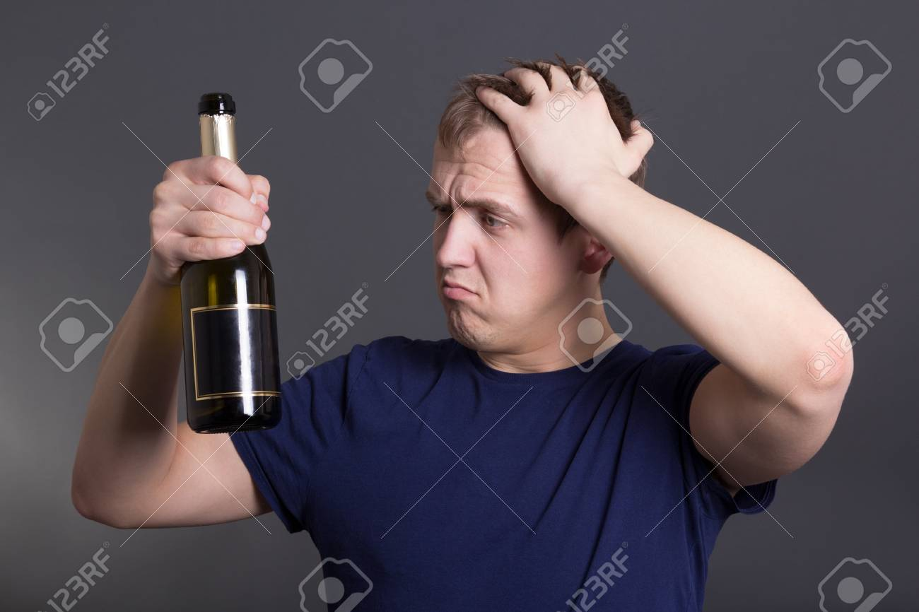 young drunk man with bottle of champagne over grey background - 18498978