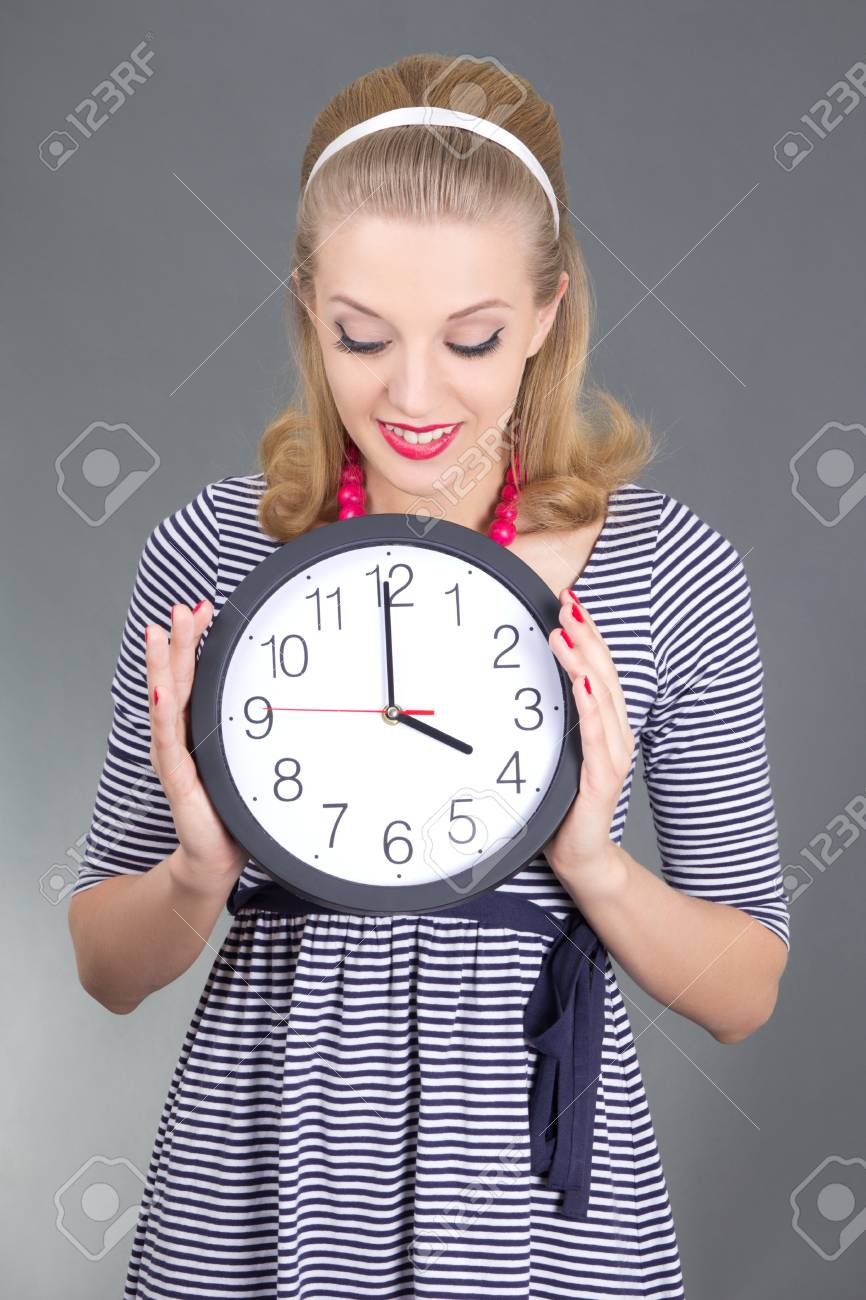 dreaming pinup girl in striped dress with clock over grey background Stock Photo - 18961400