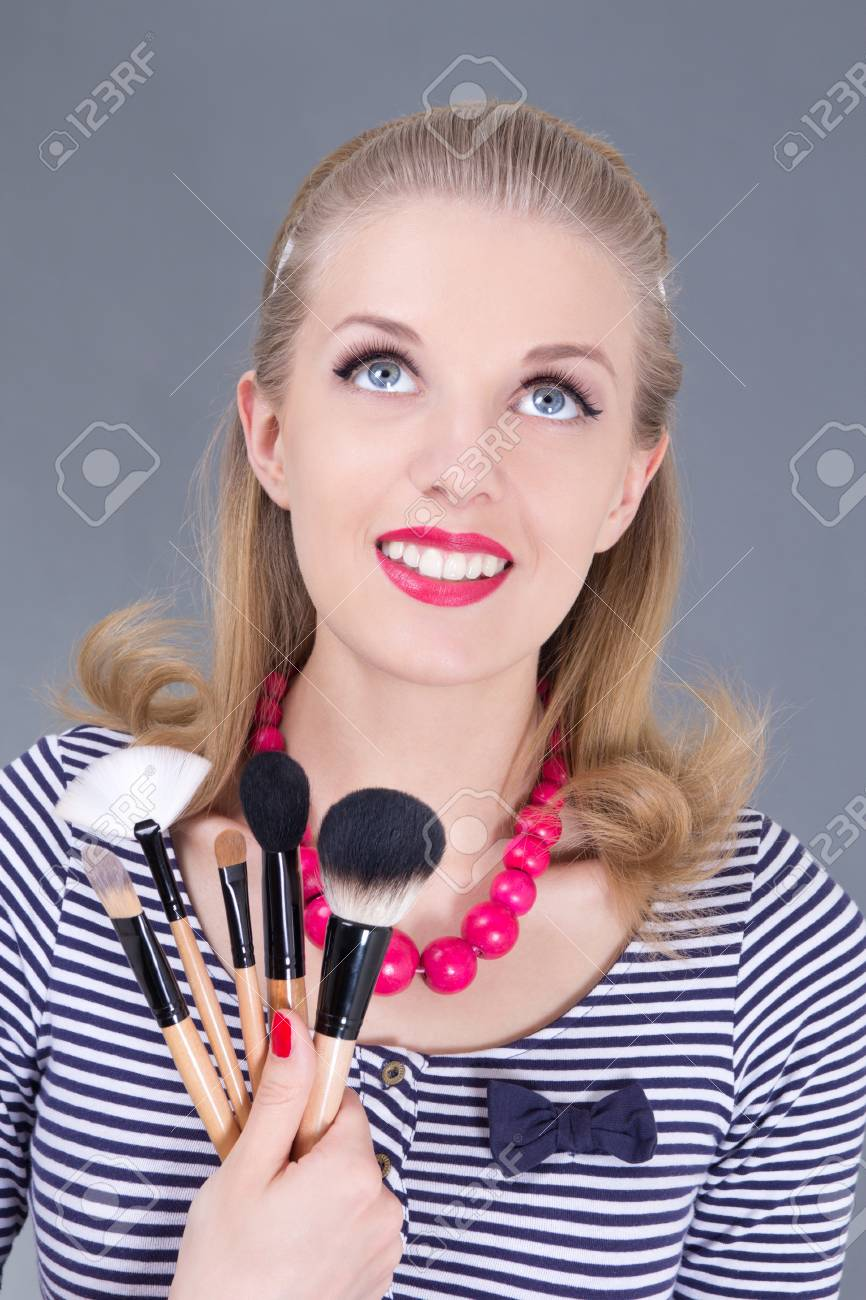 young dreaming pinup woman with make up brushes over grey Stock Photo - 18960997