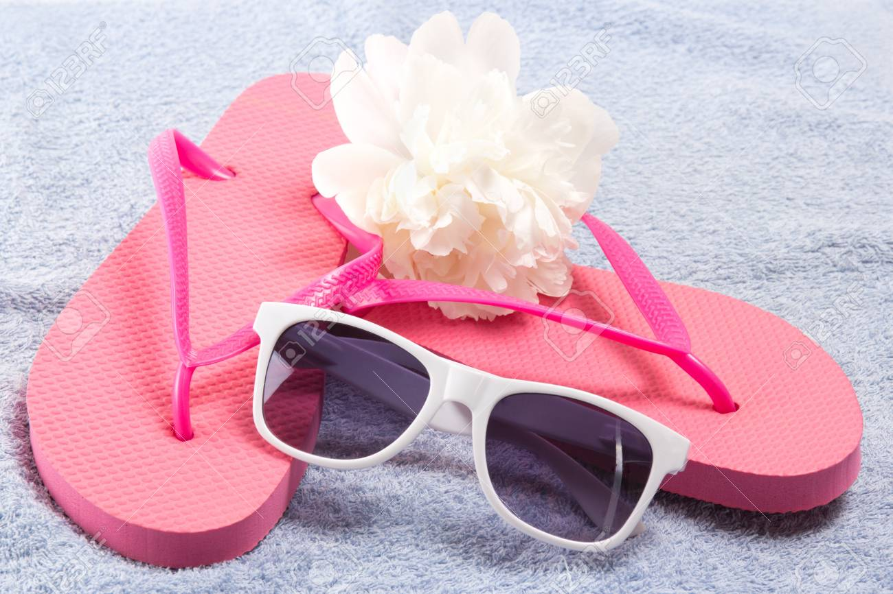 Red Flip Flops Sunglasses And White Flower Over Towel Stock Photo
