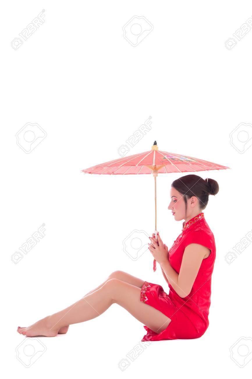 1f28deeb8 Foto de archivo - Joven y atractiva mujer sentada en vestido rojo japonés  con el paraguas aislados en fondo blanco