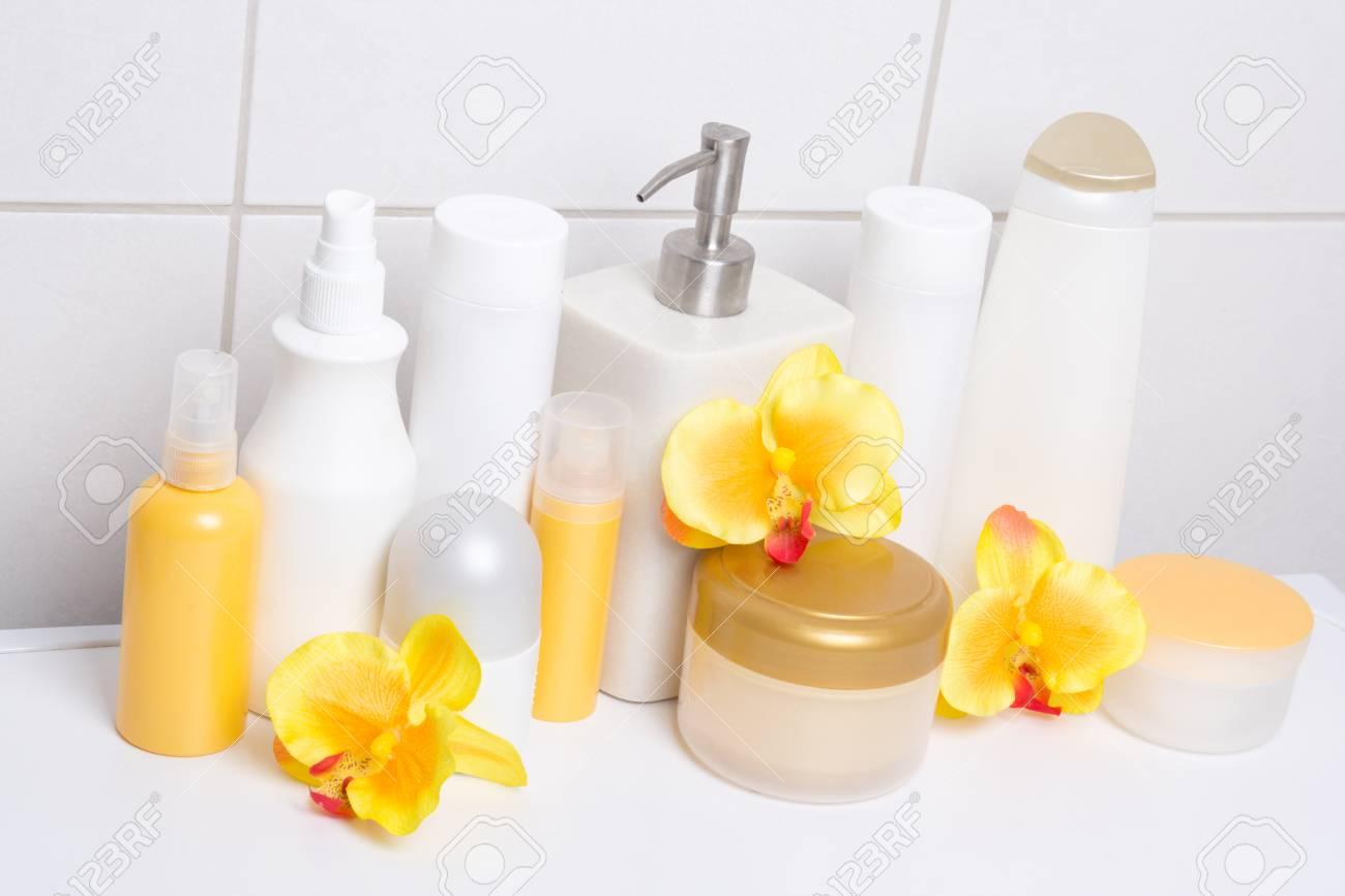 Sammlung Von Weißen Kosmetische Flaschen Und Hygieneartikel Mit  Orangefarbenen Orchideen über Geflieste Wand Im Badezimmer Standard
