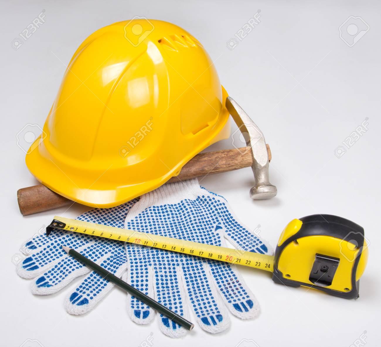 3963da8f2 Herramientas del constructor - casco amarillo, guantes de trabajo,  martillo, lápiz y cinta métrica sobre fondo blanco