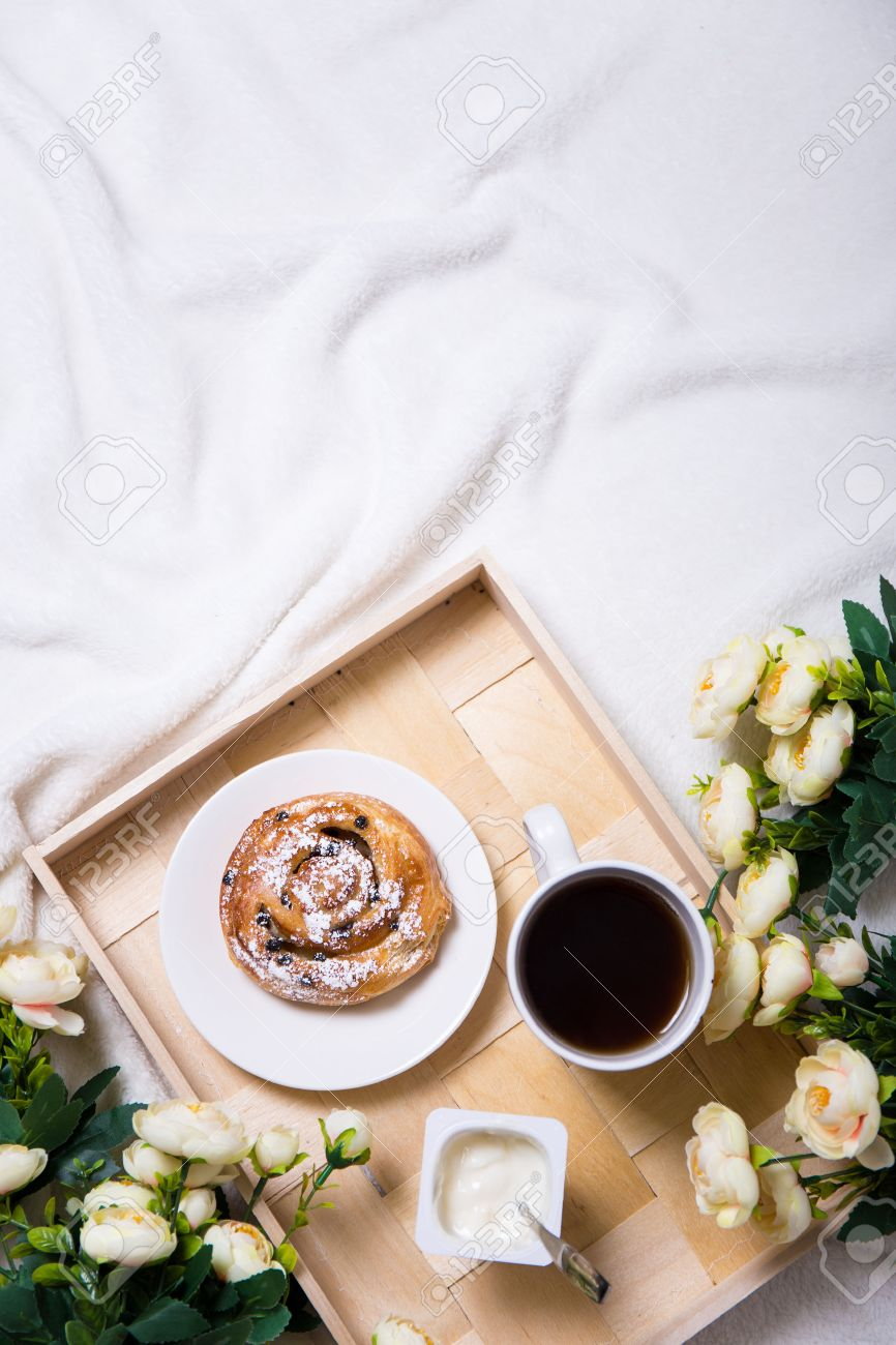 good morning - breakfast with sweet bun and tea on wooden tray and flowers in bed - 54018780