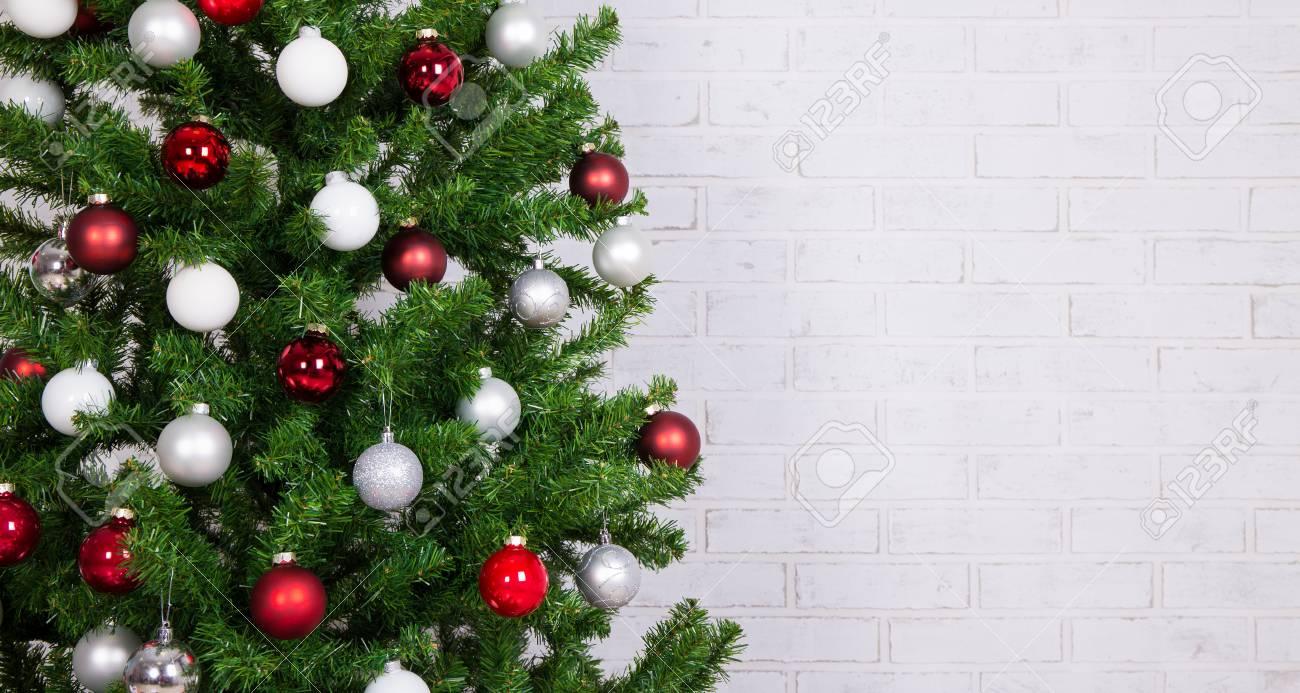 Sapin De Noel Sur Le Mur gros plan du sapin de noël décoré avec des boules colorées sur le mur de  briques blanches