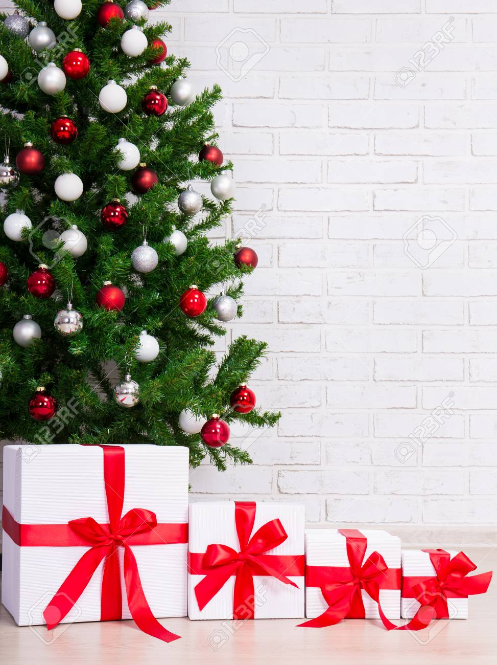 christmas background gift boxes under decorated christmas tree over brick wall stock photo 68504146
