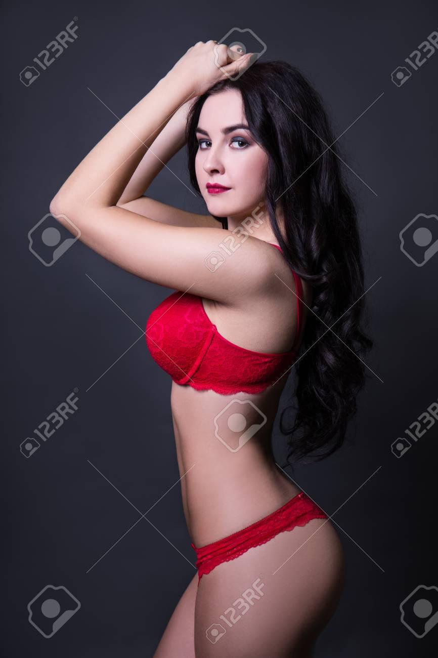 630567c25d Foto de archivo - Vista lateral de la bella mujer en lencería de encaje  rojo posando sobre fondo negro
