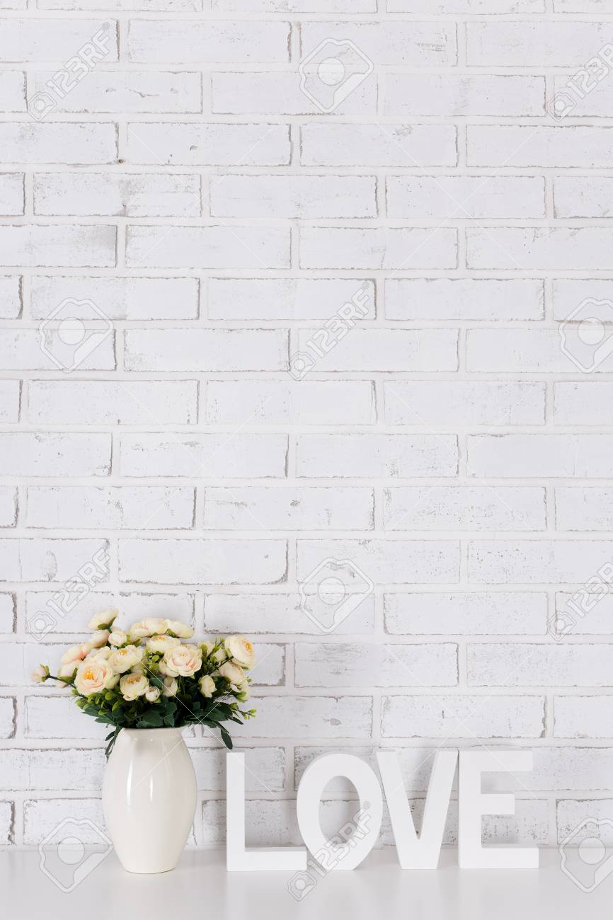White Wooden Word Love And Flowers Over White Brick Wall Background Stock Photo Picture And Royalty Free Image Image 81202696