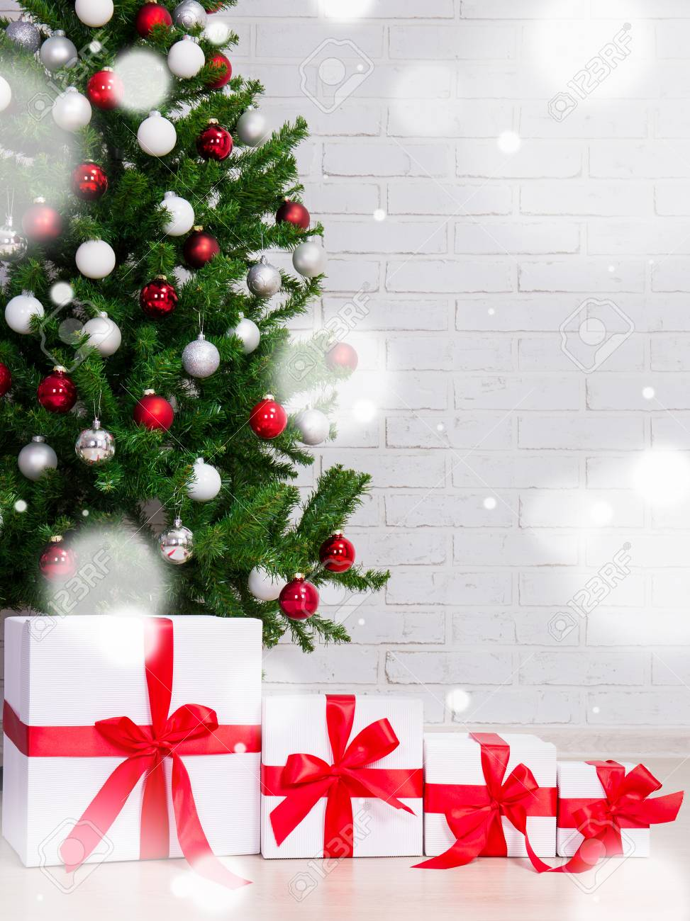 christmas background gift boxes under decorated christmas tree over brick wall and flying snow flakes