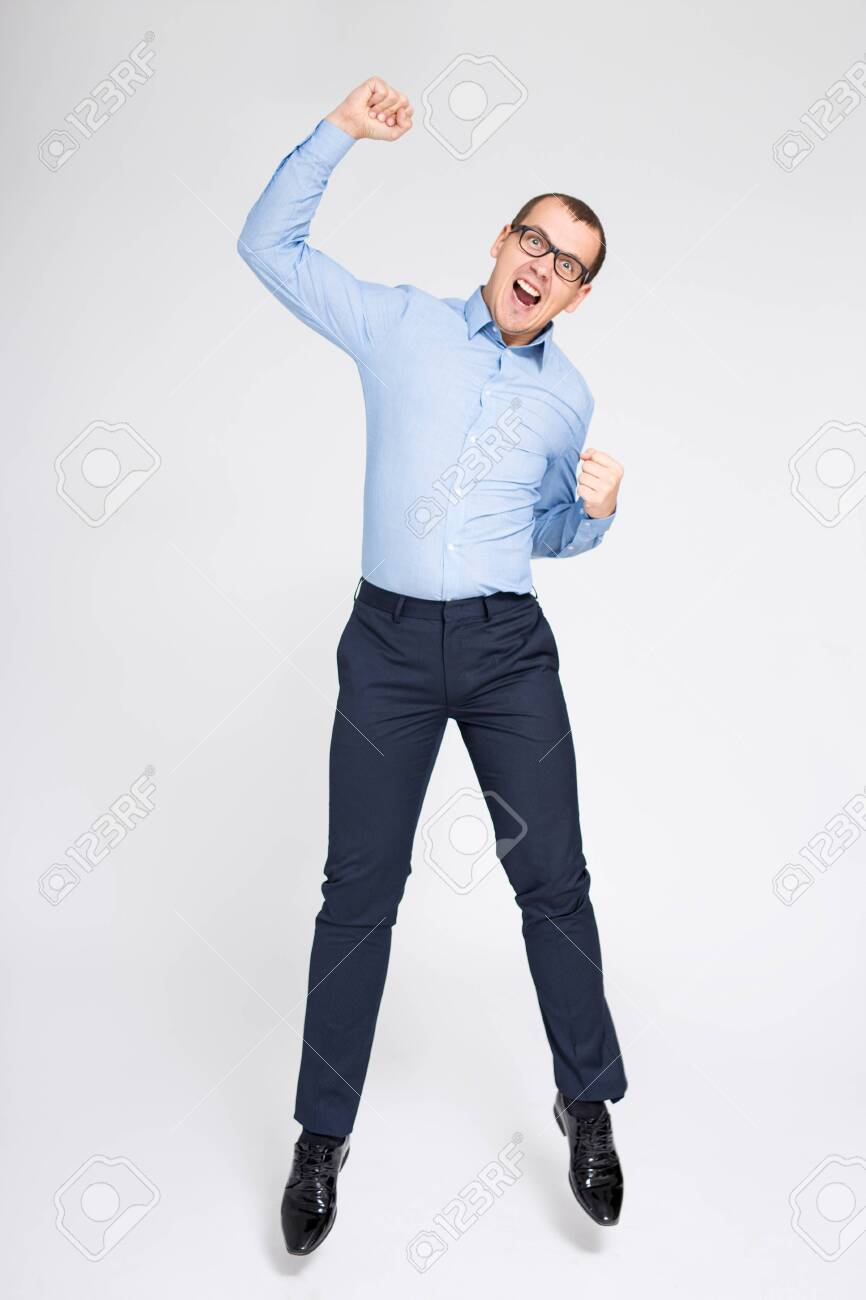 success concept - cheerful young handsome businessman celebrating something and jumping over gray background - 134721719