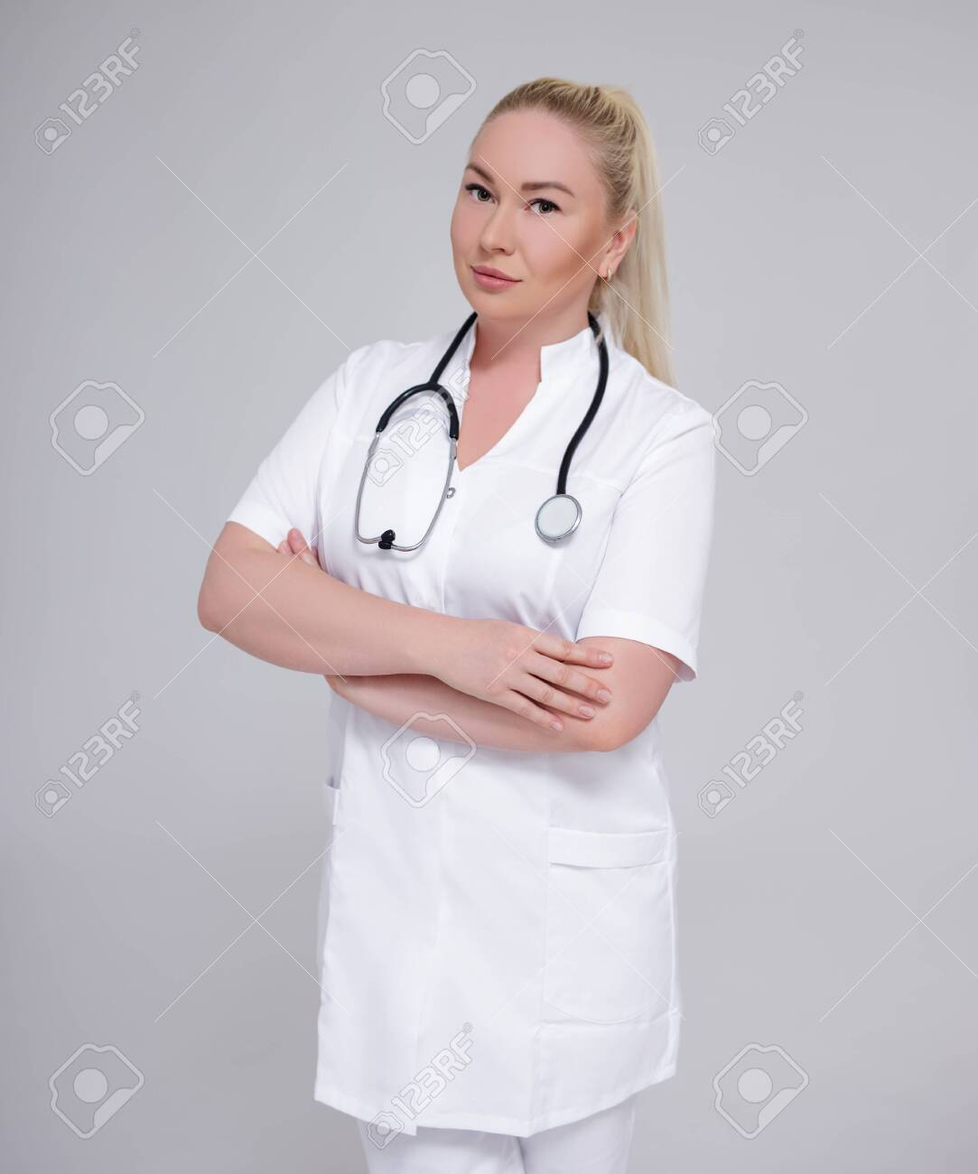 young female doctor posing over gray background - 146549228