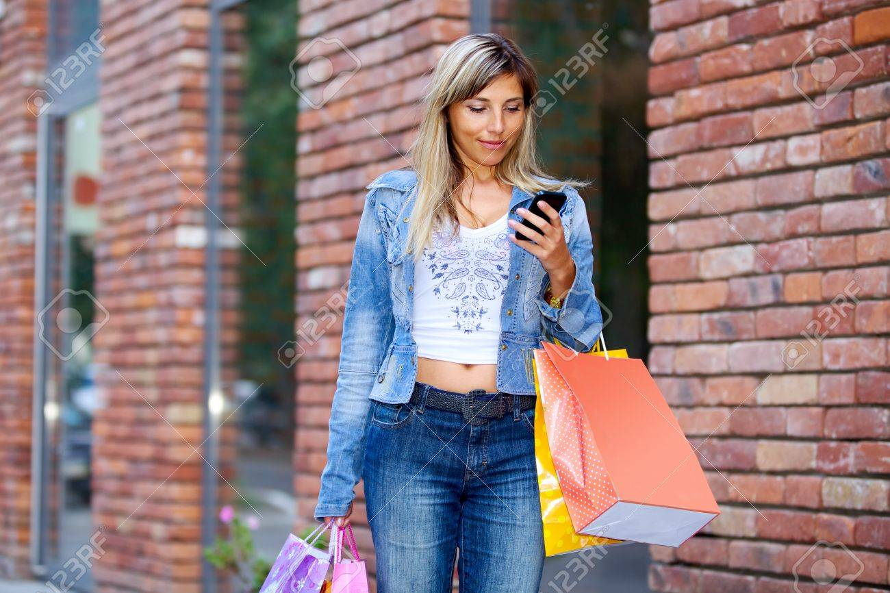 Woman with shopping bags and cellphone walking on street Stock Photo - 15415883