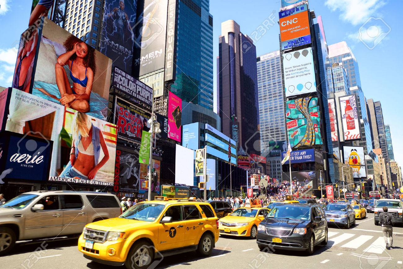 New York, New York, USA - May 08, 2016: Cars and taxi cabs on 7th Avenue and Broadway in Times Square with crowds of people and lots of advertising - 59111545