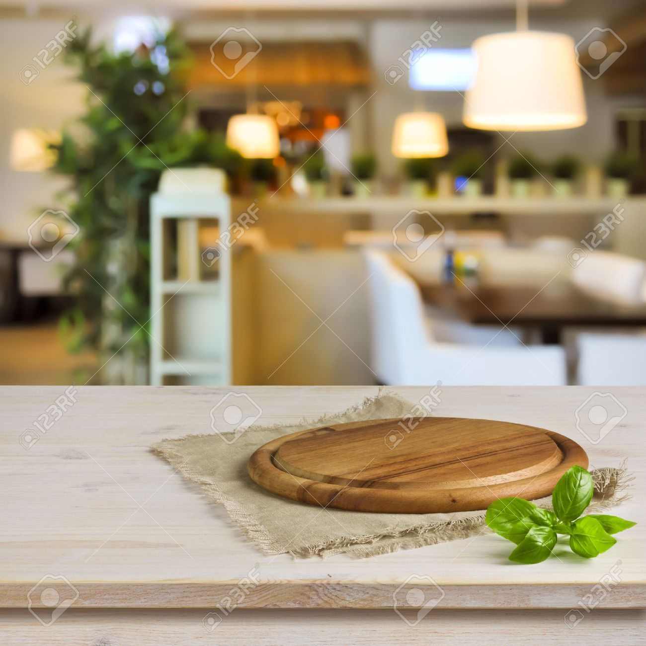 Cutting board on table over blurred restaurant interior background - 37834903