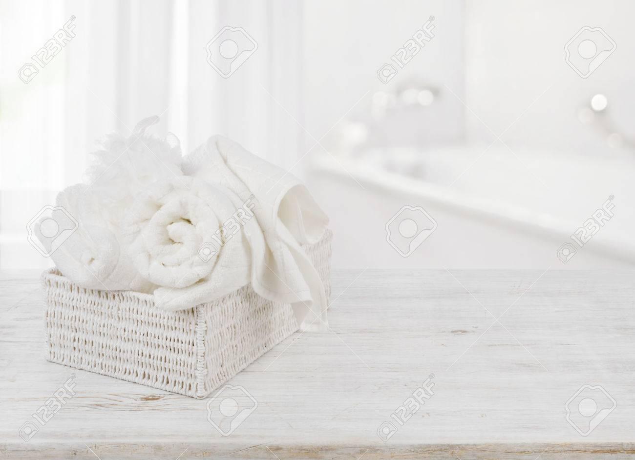 serviettes et éponge de bain en boîte sur fond de salle de bain flou