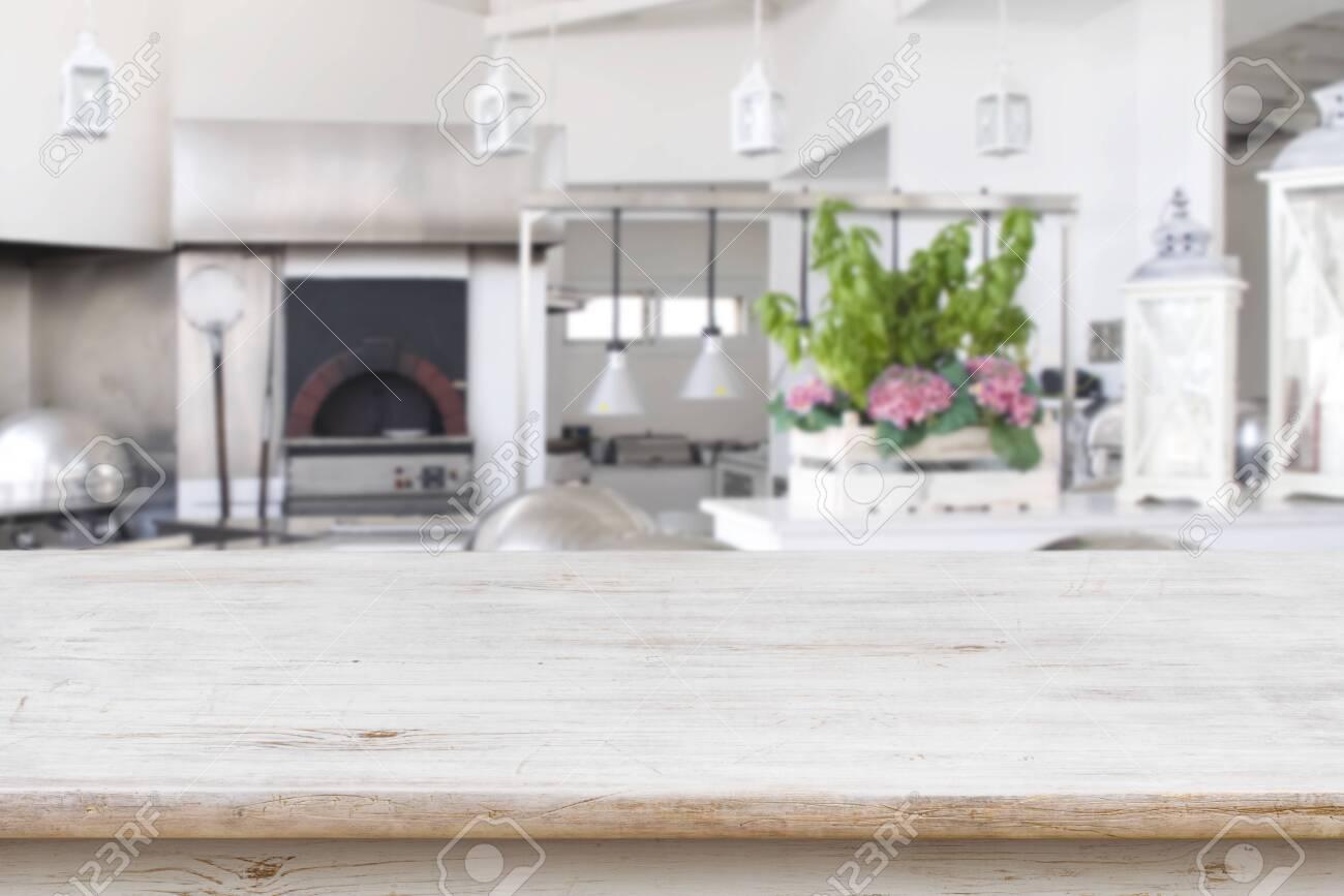 Wooden table top on blurred modern restaurant kitchen room - 128010071