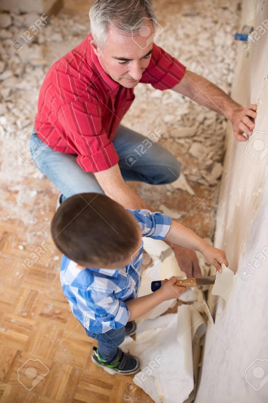 孫は壁紙を削除する彼の祖父を助けて クローズ アップ の写真素材 画像素材 Image