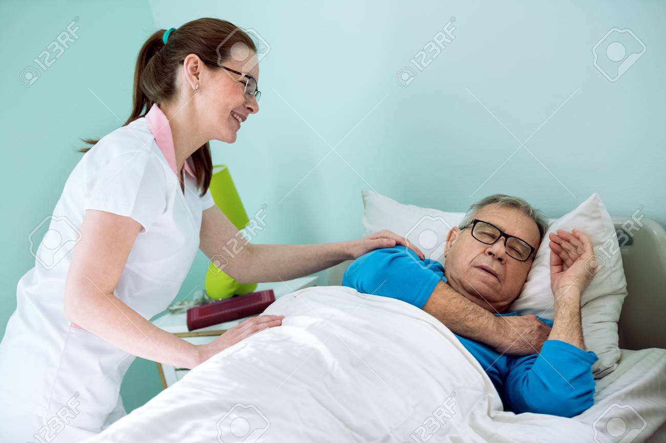 Nice Smiling Nurse Looking At Patient Who Sleeping And Dreaming Nursing Home Care For