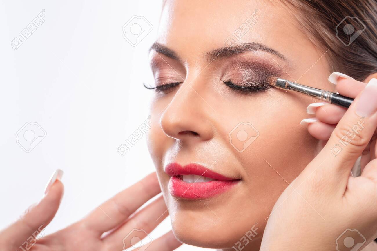 Close up of a pretty face while applying makeup, matching skin tan - 147517981