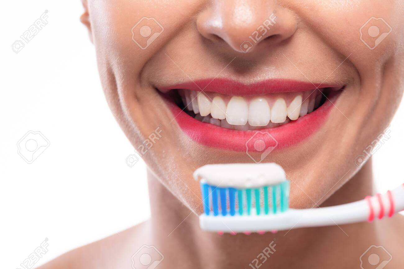 Close up of white teeth and a toothbrush with some toothpaste on it - 147863974