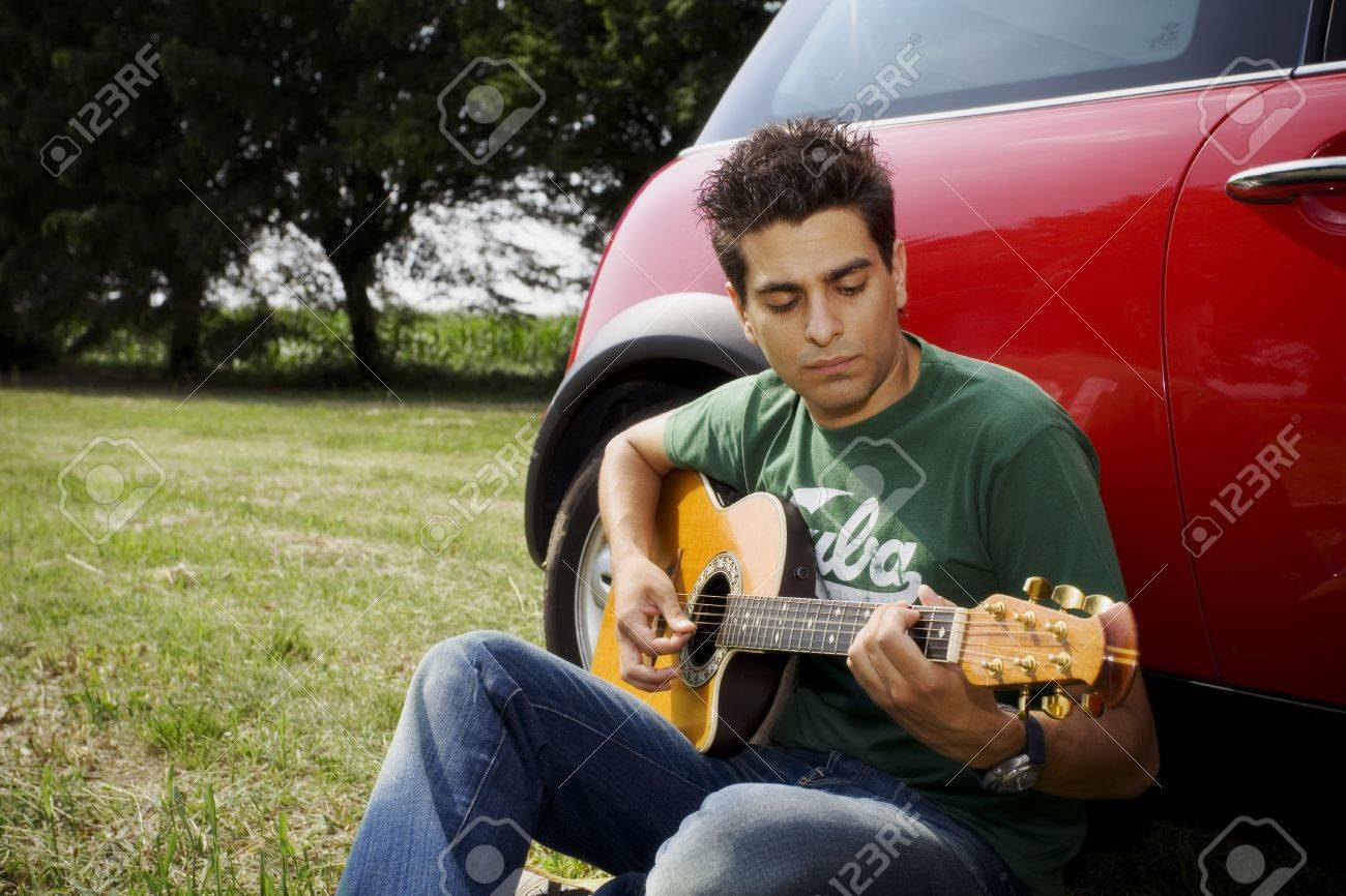 cool guy playing guitar besides his car Stock Photo - 463141