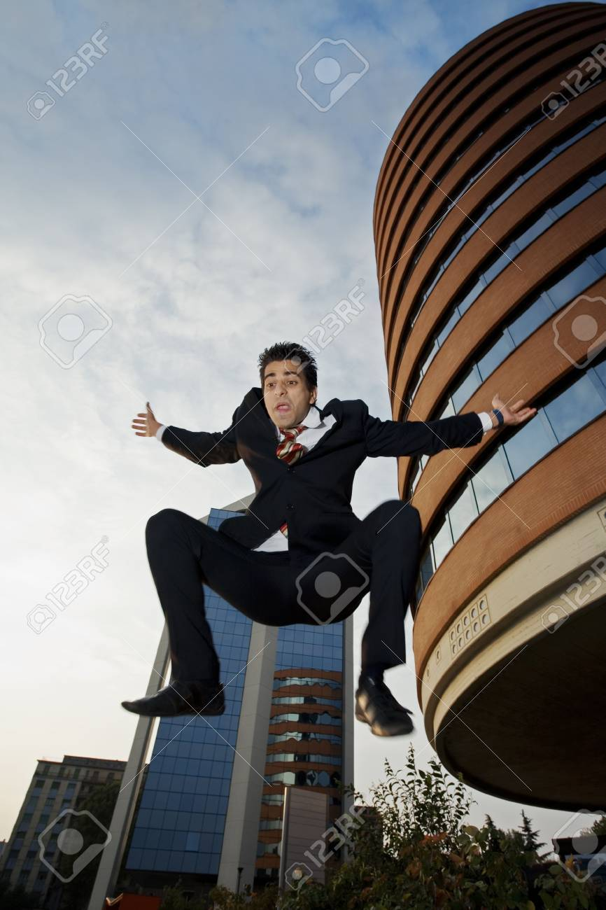 desperate businessman jumping out of a building and screaming. The head is in clear focus and the body is a bit blurred Stock Photo - 587133