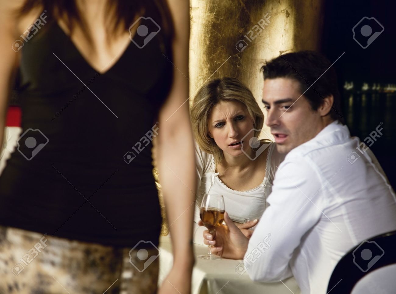 girls night out: horny guy looking at a nice girl passing by...while dining out with his girlfriend! Stock Photo - 888933