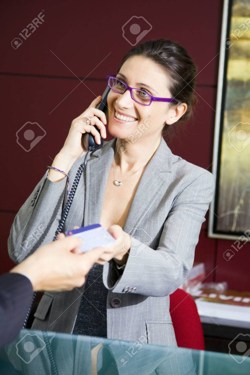 Paying by credit card: young salesclerk smiling at a customer Stock Photo - 1504723