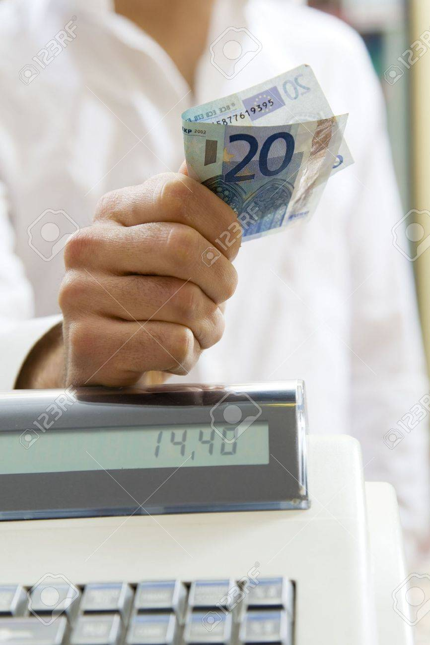 man at the supermarket standing near the cash box and holding 20 Euro Stock Photo - 2767140