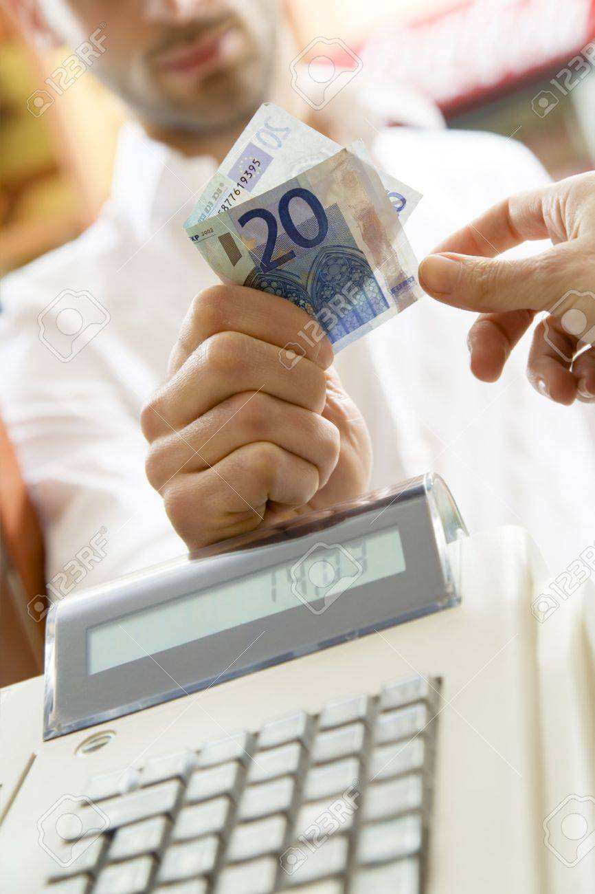 man at the supermarket giving 20 Euro to the cashier Stock Photo - 2779953