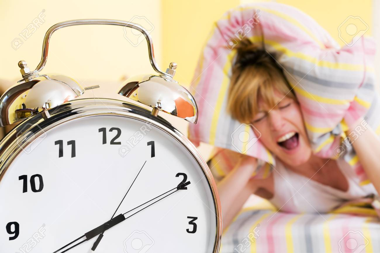 Close up of alarm clock. Young woman in the background covering ears with pillow. Stock Photo - 2933628