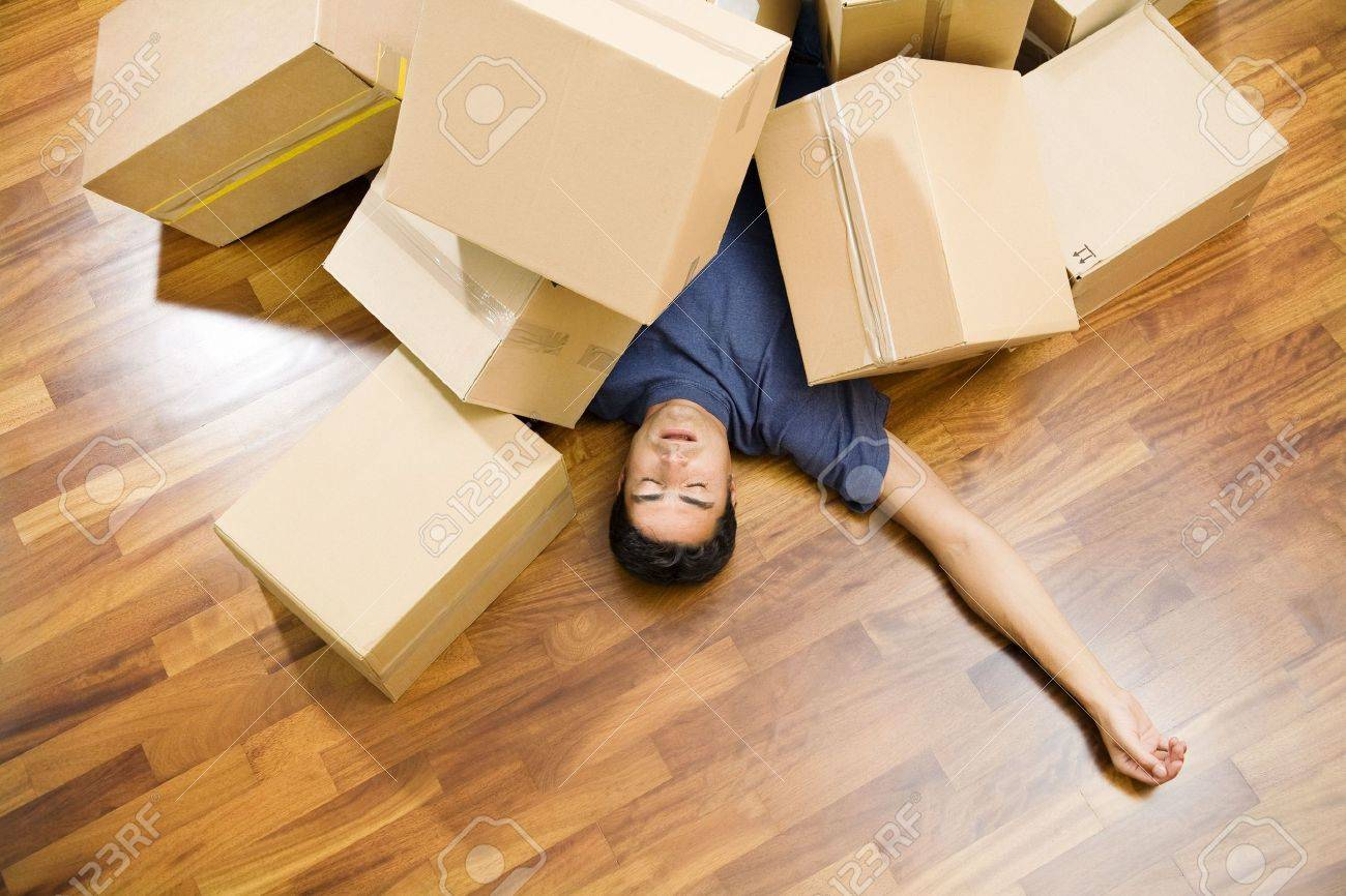 High angle view of young man sleeping underneath moving boxes Stock Photo - 3336142