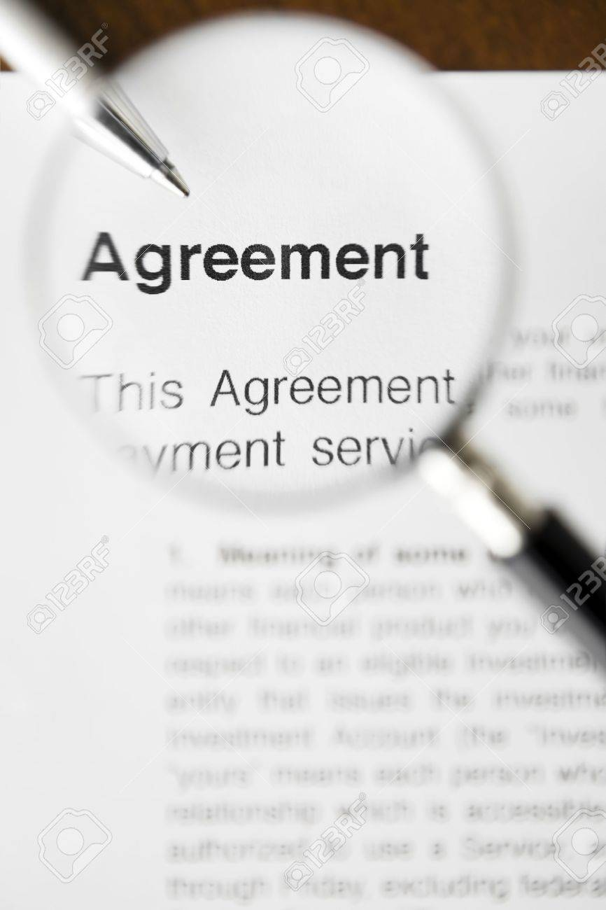 Magnifying glass over agreement paperwork and pen Stock Photo - 3663842