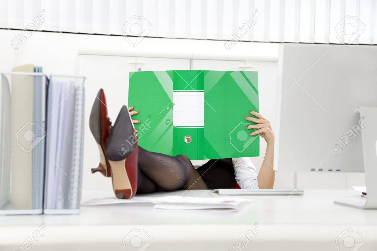 Young businesswoman sitting at desk with legs up and looking at folder Stock Photo - 3951270