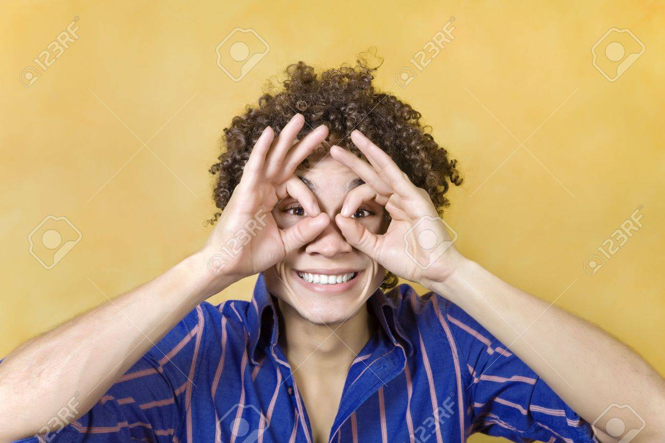 young man with hand over eyes, looking through fingers Stock Photo - 4186130