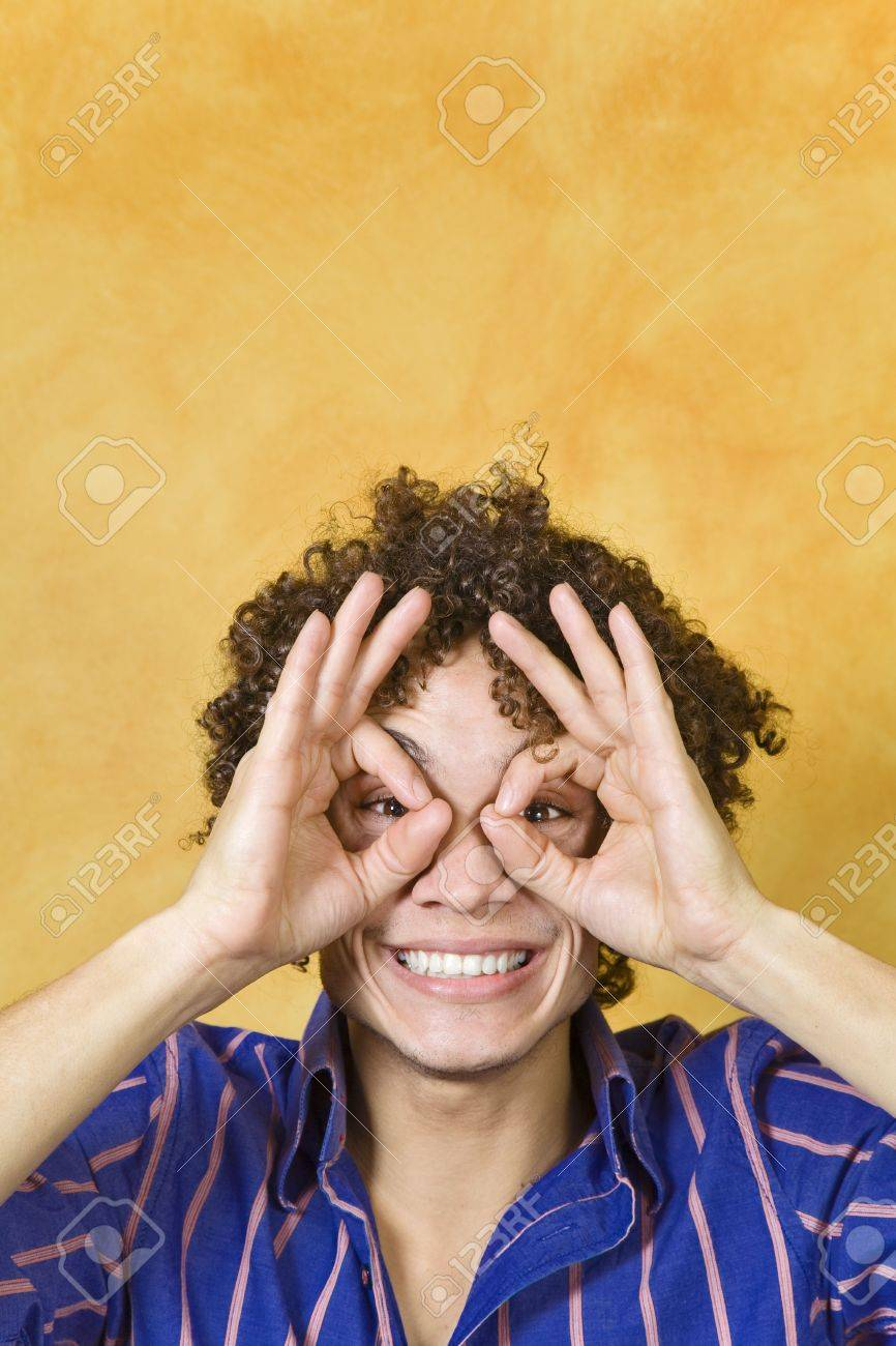 young man with hand over eyes, looking through fingers Stock Photo - 4313610