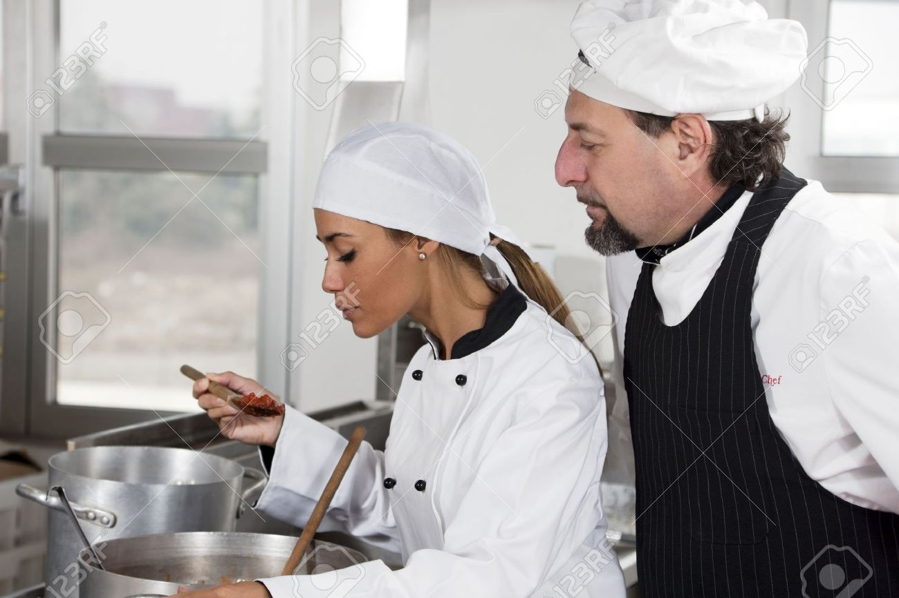 young chef and mature chef tasting tomato sauce. Stock Photo - 4563079