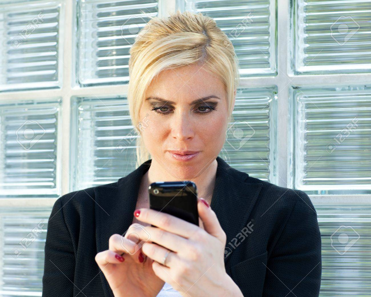 mid adult businesswoman reading phone message on smartphone. Stock Photo - 4852270