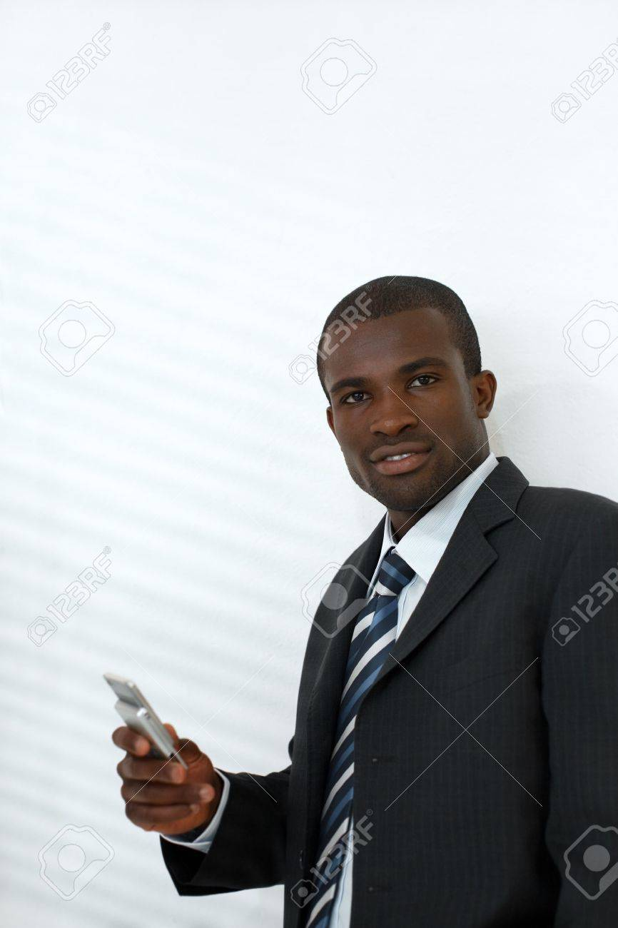 young adult businessman holding mobile phone. Shadows from venetian blinds on wall. Copy space Stock Photo - 4904787
