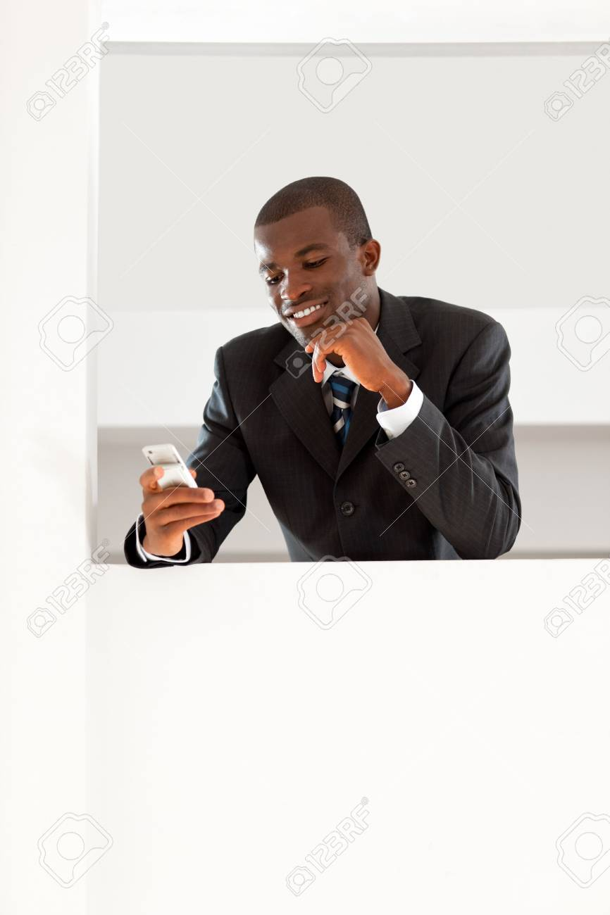 young adult afro-american businessman reading emails on his smartphone indoors. Copy space Stock Photo - 4945812