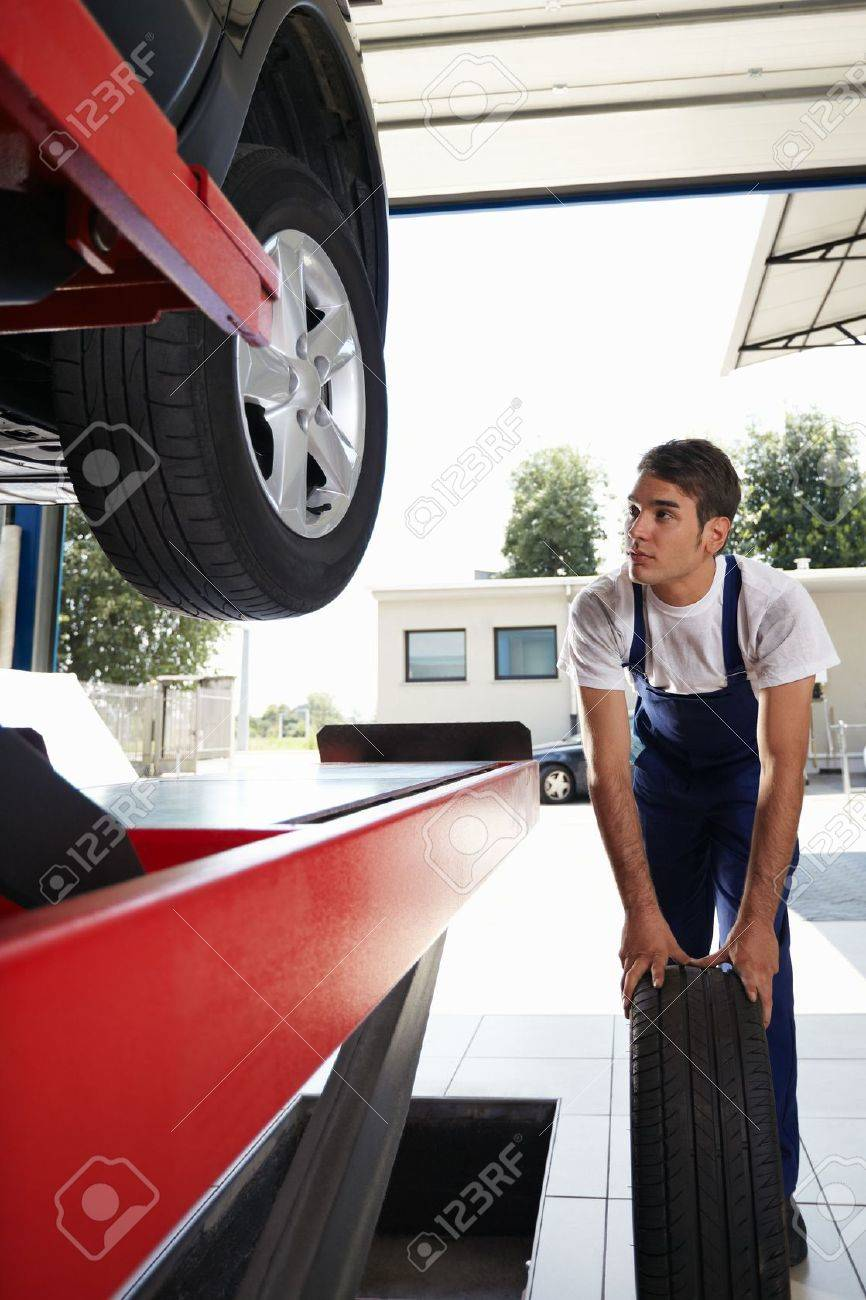 mechanic replacing car tyre in auto repair shop. Front view Stock Photo - 5233699
