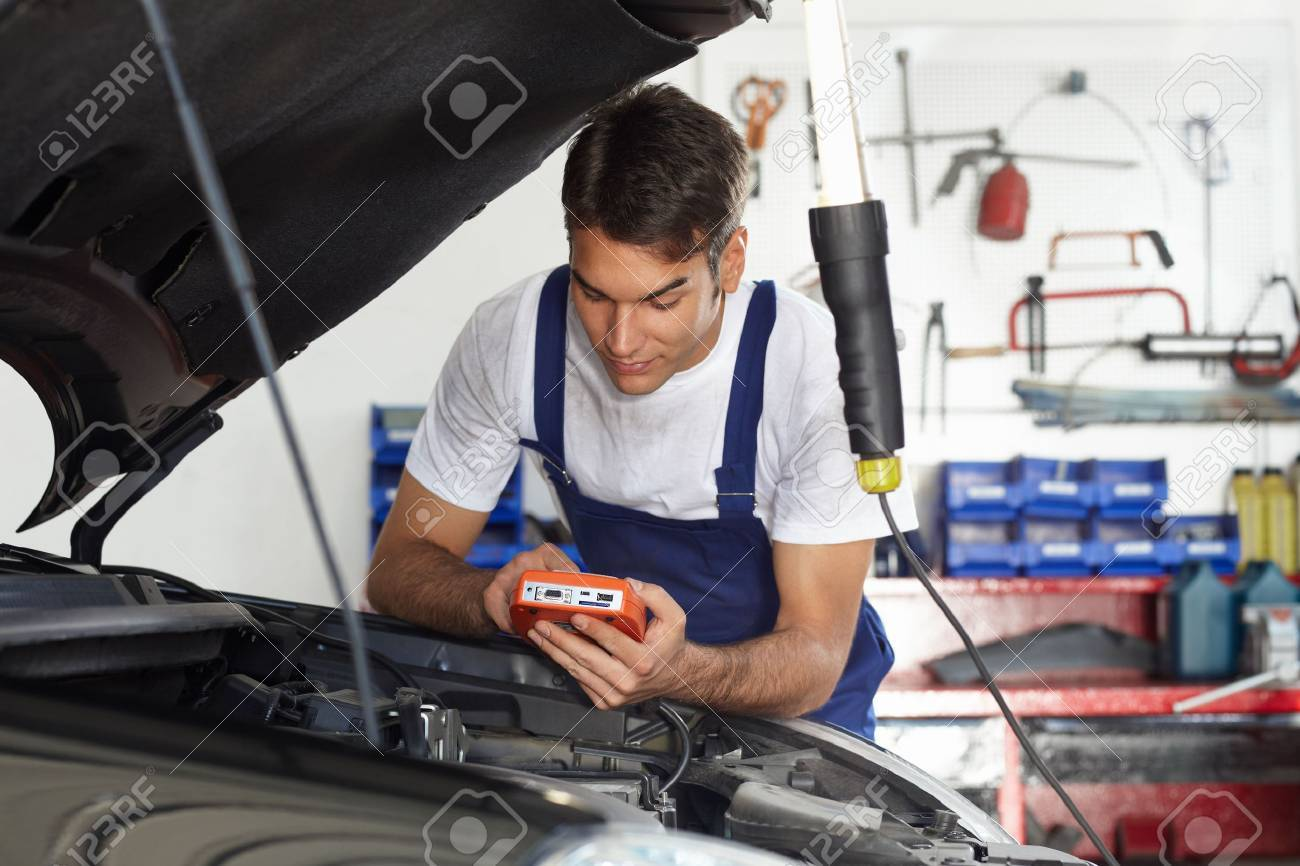 mechanic leaning on bonnet with tester equipment Stock Photo - 5263081