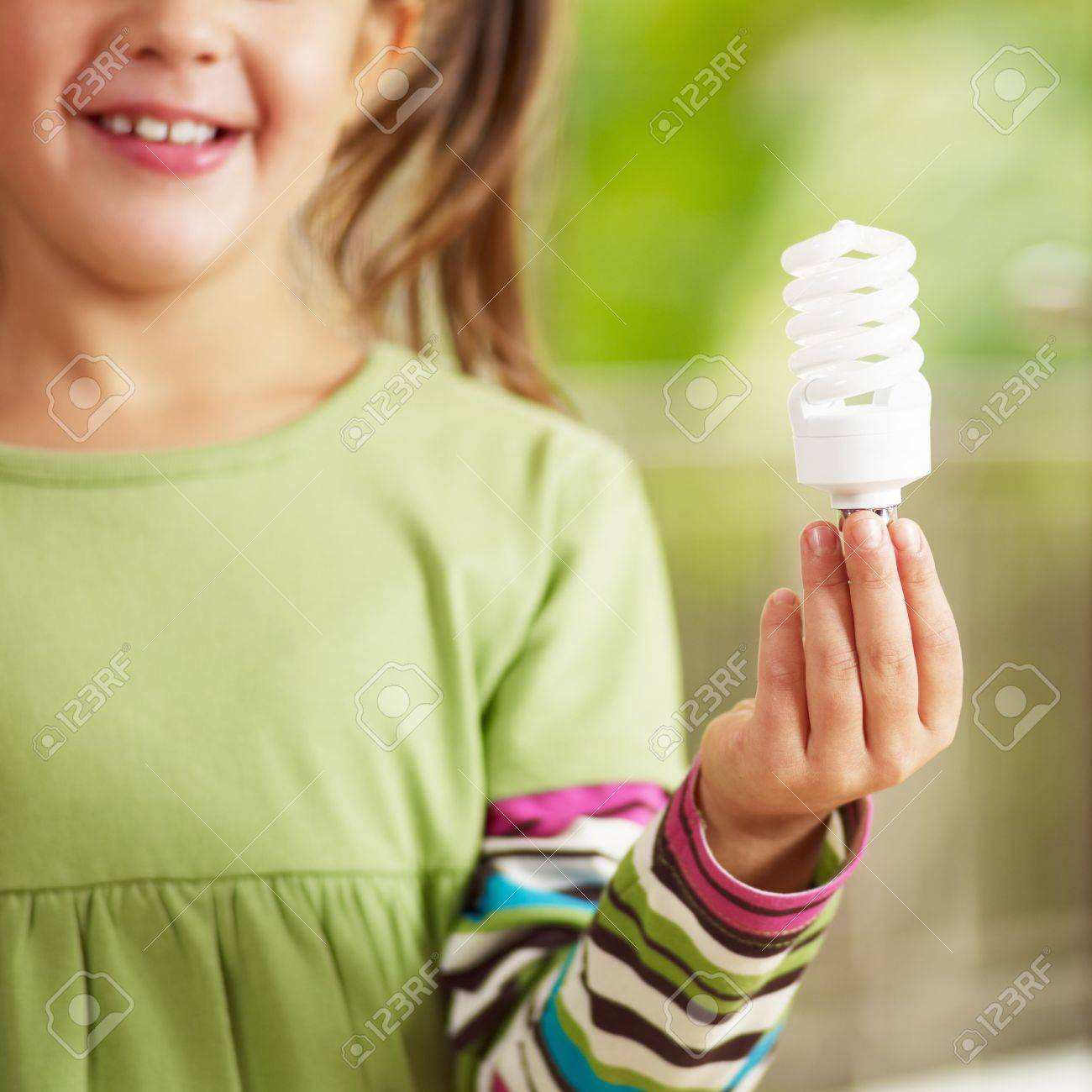 Girl holding light bulb and smiling. Selective focus Stock Photo - 5746741