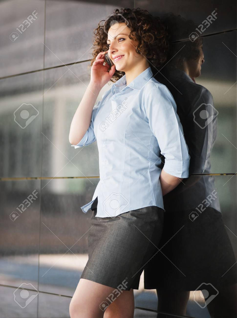 italian businesswoman talking on mobile phone outdoors and smiling. Vertical shape Stock Photo - 6877715