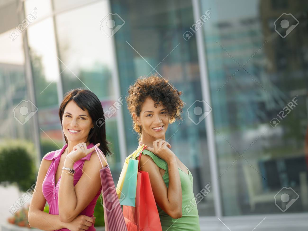 mid adult italian woman and hispanic woman carrying shopping bags out of shopping center. Horizontal shape, waist up, copy space Stock Photo - 7380431