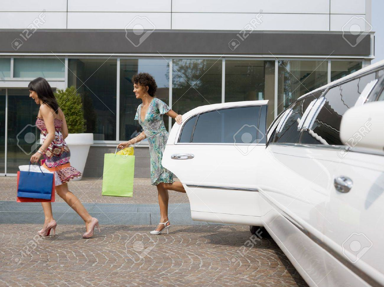 two women running out of limousine with shopping bags. Horizontal shape, full length Stock Photo - 7664819