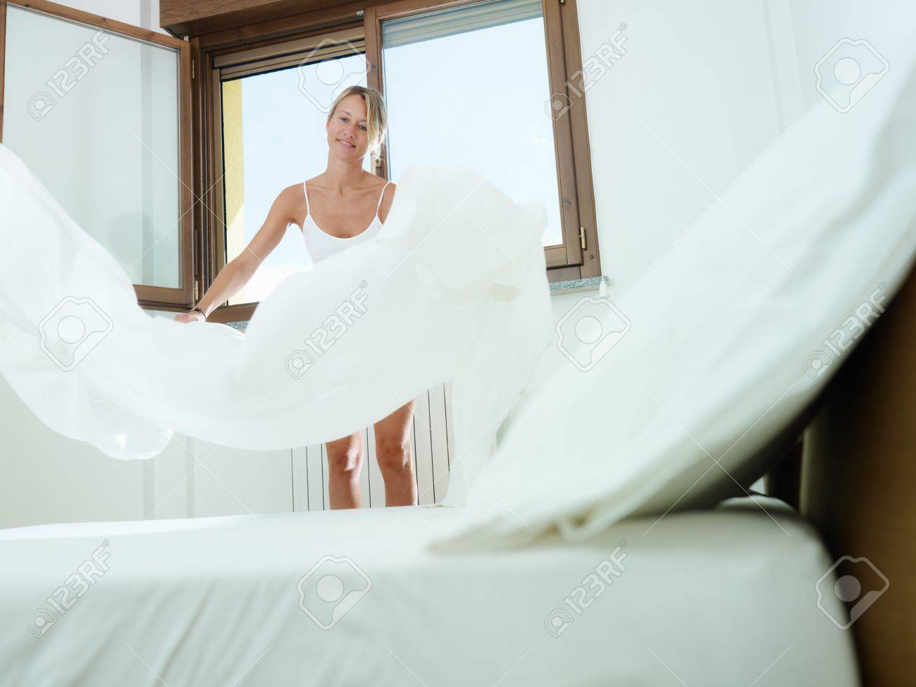 mid adult woman making bed with white sheet. Horizontal shape, low angle view Stock Photo - 7664846
