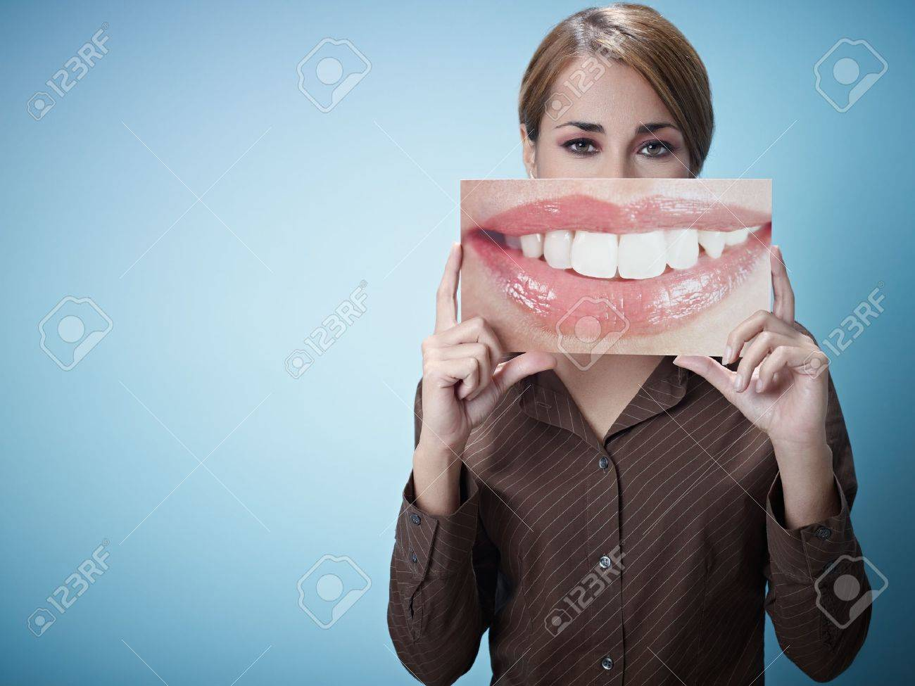 mid adult business woman holding photo of toothy smile on blue background. Horizontal shape, front view, waist up, copy space Stock Photo - 8324098
