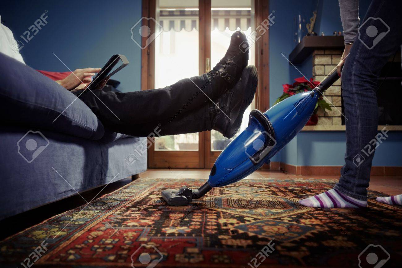 caucasian heterosexual couple, with woman doing chores using vacuum cleaner on carpet and lazy man on sofa with tablet pc. Horizontal shape, low angle view Stock Photo - 8843075