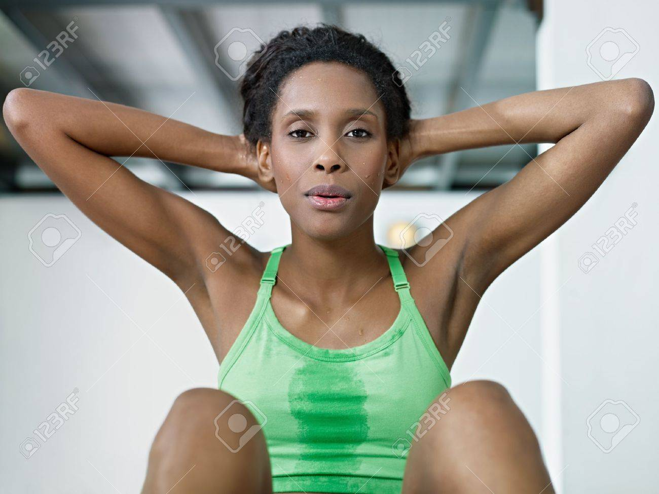 young camel toe Stock Photo - young african american woman in green sportswear exercising  abdominals in fitness club, looking at camera. Horizontal shape, front  view, ...